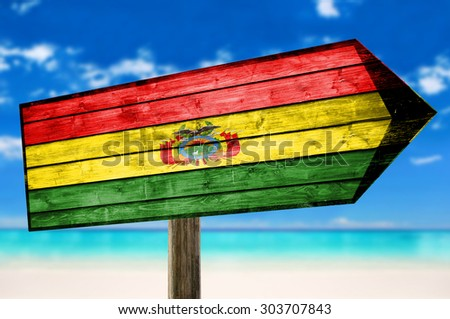 Bolivia Flag on wooden table sign on beach background