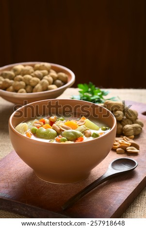 Bolivian Sopa de Mani (peanut soup) made of meat, pasta, vegetables, ground peanut, photographed with natural light (Selective Focus, Focus one third into the soup)  - stock photo