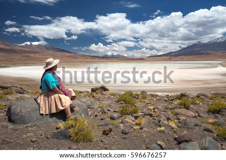 Bolivian woman in traditional costume on a high-altitude lagoon on the plateau Altiplano, Bolivia