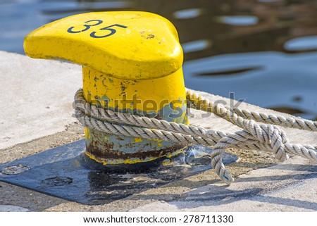 Bollard with mooring line - stock photo