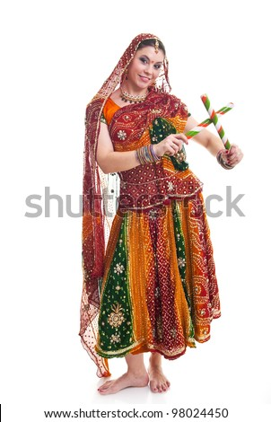 Bollywood dancer in traditional beautiful orange dress with veil and sticks - stock photo
