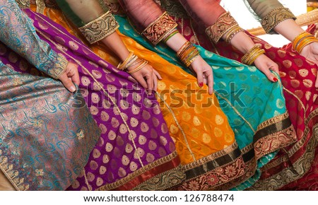 Bollywood dancers are holding their vivid costumes. Hands are in a row - stock photo