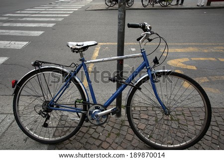 BOLOGNA, ITALY - APRIL 19, 2014: A bicycle stands locked to a pole on a street in Bologna, Italy, on Saturday, April 19, 2014.  - stock photo