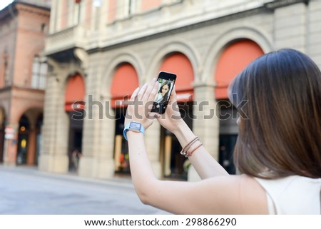 BOLOGNA, ITALY - June 12, 2015:  One girl takes a selphie with an iphone6 and an iwatch. - stock photo