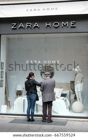 Bologna, Italy, 1 May 2017 - an old man and a woman look at the showcase of the Zara Home furnishing store in Bologna