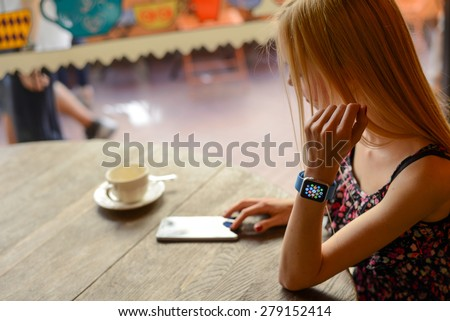 BOLOGNA, ITALY - MAY 17, 2015:  One girl wears the apple watch in a bar using the iphone 6. - stock photo