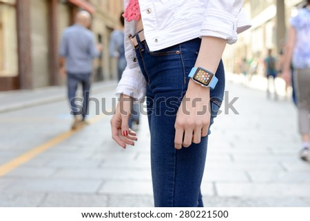 BOLOGNA, ITALY - MAY 17, 2015: One girl wears the apple watch in the city center - stock photo
