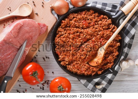 Bolognese sauce cooking in a frying pan and ingredients on the table. horizontal view from above