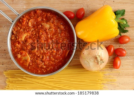 Bolognese sauce in pot with dry pasta and vegetables - stock photo