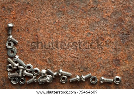 Bolts and nuts on rusted iron plate with copy space for text - stock photo