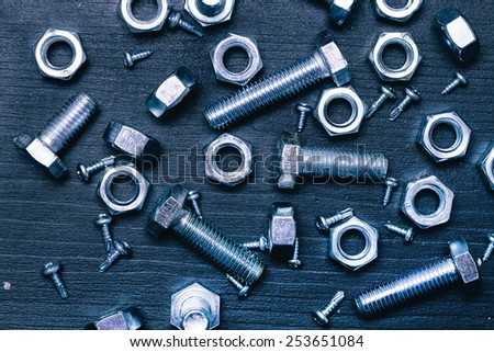Bolts and nuts on the wooden table - stock photo