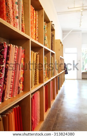 Bolts of colorful fabric on shelves - stock photo
