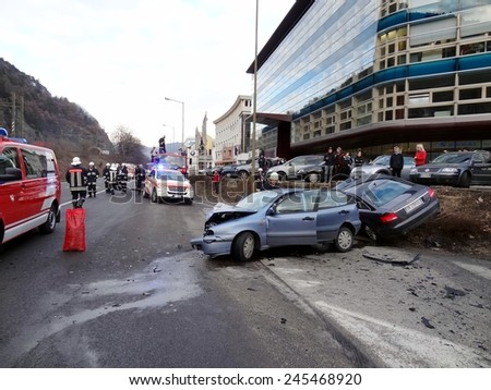 BOLZANO BOZEN, ITALY - JANUARY 20, 2015: Paramedics and Firemens provide first aid to injured motorist after hard collision between two cars on the iced road  in winter time on January 20, 2015. - stock photo
