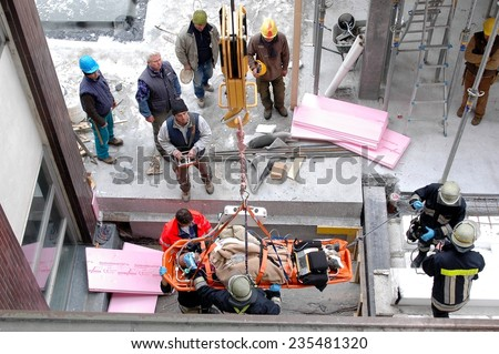 BOLZANO - ITALY, FEBRUARY 2, 2014: Firefighters and paramedics rescue a construction worker after crash. Male worker lying on the floor outside areal of a building site in Bolzano in February 2, 2014 - stock photo