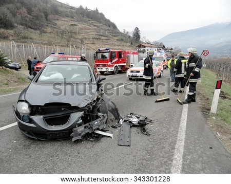 BOLZANO, ITALY - NOVEMBER 25, 2015: Firefighters and Paramedics at work after hard collision between two cars on the road. Car accident after hitting a patch of ice on November 25, 2015. - stock photo