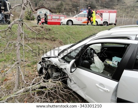 BOLZANO, ITALY - NOVEMBER 25, 2015: Firefighters and Paramedics in the background after hard collision between two cars on the road. Suv Car off road in the field after crash on November 25, 2015. - stock photo