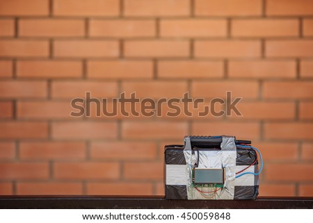 bomb with radio control and digital countdown timer bomb on the brick wall background. terrorism and dangerous life concept - stock photo