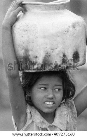 BOMBAY, INDIA - FEBRUARY 15, 1984: young girl carrying an heavy pot of water. The work of many children contribute to modernize the city.