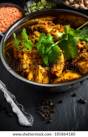 Bombay spiced potatoes and cubed chicken thighs with coriander leaves. Shot in natural light with lentils and chickpeas. The perfect image for a restaurant cover design. - stock photo