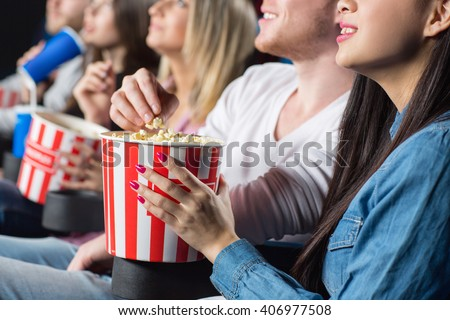 Bon appetit! Closeup shot of a young woman feeding her cheerful laughing man with popcorn at the movie theater - stock photo