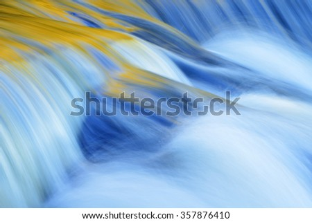 Bond Falls cascade captured with motion blur and illuminated with reflected color form sunlit autumn foliage, and blue sky overhead, Michigan's Upper Peninsula, USA - stock photo