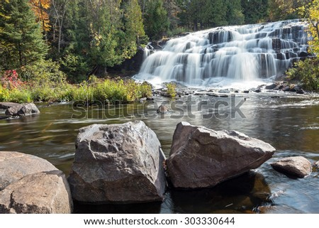 Bond Falls in Autumn - Bond Falls rushes with water after autumn rains swell the river. Large rocks layer the foreground on this sunny day. - stock photo