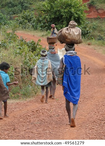Bonda tribal women carry trade goods to  weekly market on Nov 12, 2009 in Ankadeli, Orissa in India