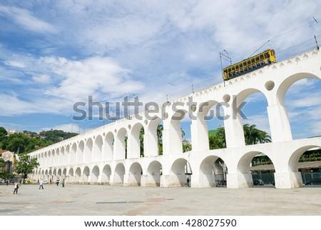 Bonde de Santa Teresa tram train drives along distinctive white arches of the landmark Arcos da Lapa Arches in Centro of Rio de Janeiro Brazil - stock photo