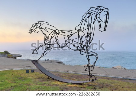 BONDI, AUSTRALIA -  OCTOBER 25, 2014; Sculpture by the Sea annual free public  event 2014.  A sea fog rolls in behind the sculpture titled Which Way Forwards by  Harrie Fasher, NSW.    - stock photo