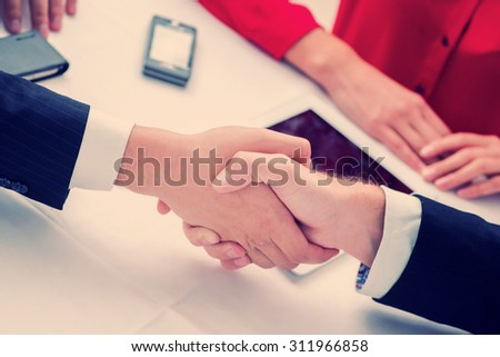 Bonding company. Three successful and confident businesspeople shake hands. Businesspeople in formal attire sitting in an office at a desk and smiling at the camera - stock photo