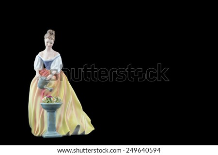 Bone China Figurine Wearing a White and Yellow Dress, isolated on a black background