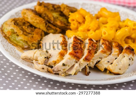 Boneless breast of chicken seasoned with rosemary and lemon and grilled to golden brown.  Served with fried green tomatoes and macaroni and cheese. - stock photo