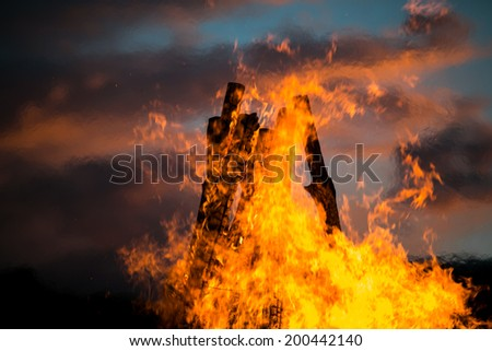 Bonfire in a white summer night with beautiful sunset sky - stock photo