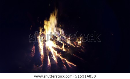 Bonfire lit at a picnic in a forest with sausages