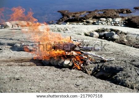 Bonfire on the rocks by a lake - stock photo