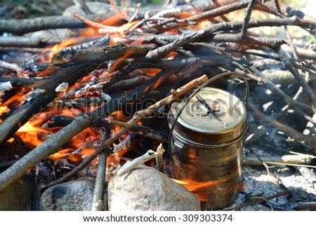 Bonfire on which is brewed pot. - stock photo