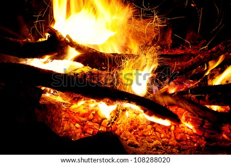 Bonfire with flame close up at night time - stock photo