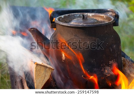 Bonfire with metal old black boiling teapot  - stock photo