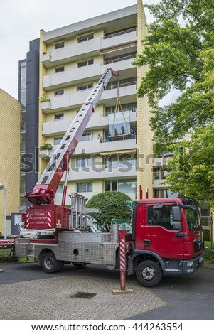 BONN, GERMANY, 2016-06-20: Lifting a big Window with a heavy crane to a multistory building for replacement