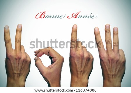 bonne annee, happy new year written in french, with hands forming number 2013 - stock photo