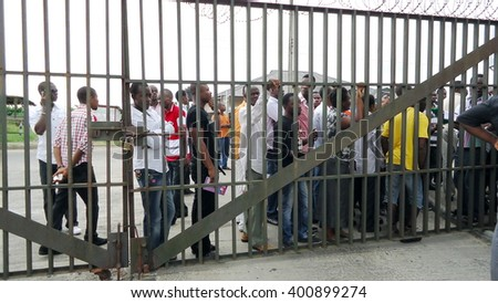 BONNY ISLAND, NIGERIA - APRIL 5, 2013: Locals wait outside the gates of a vocational center to take tests in pursuit of a job - stock photo