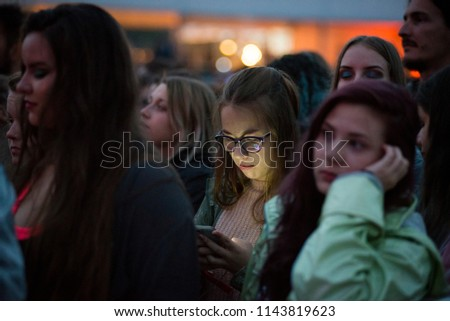 BONTIDA, ROMANIA - JULY 18, 2018: A young girl checking her smart phone during a live concert at Electric Castle festival