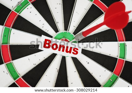 Bonus Concept and a dart in center of target - stock photo