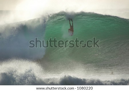 Boobie board rider catches a wave at Bonzai Pipeline off of Oahu's North Shore. (image contains noise) - stock photo