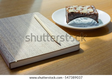 book and brownie  on wooden table in break time