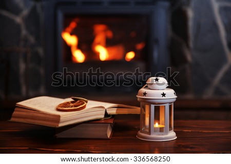 Book and candles on vintage wood table. Fireplace as background - stock photo