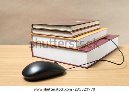 book and computer mouse on wood background - stock photo