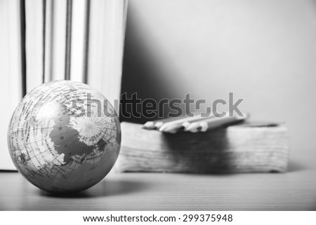 book and earth ball with color pencil on wood background black and white color tone style - stock photo