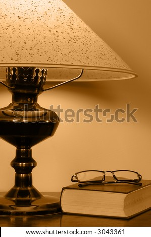 Book and glasses lying close by bedside lamp.