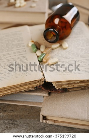 Book and pills on wooden table closeup